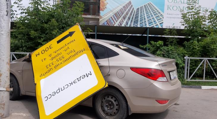 На улице Дзержинского на припаркованный автомобиль упал рекламный знак